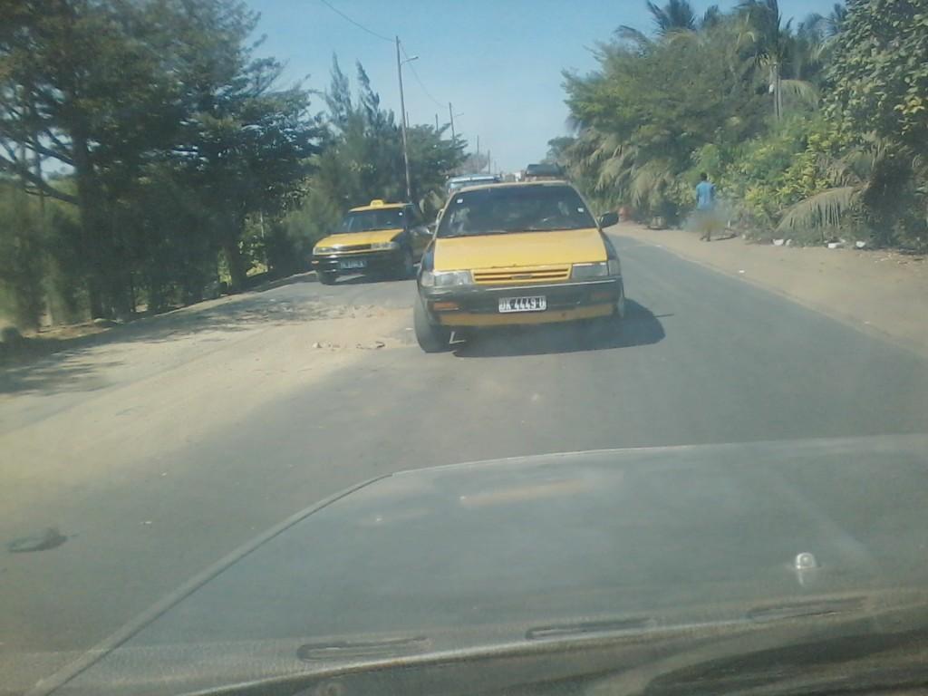 Ce véhicule taxi est obligé de se déporter sur gauche pour éviter ce grand trou. C'est sur l'axe entre Croisement Cambérène et Rond-Point La Case